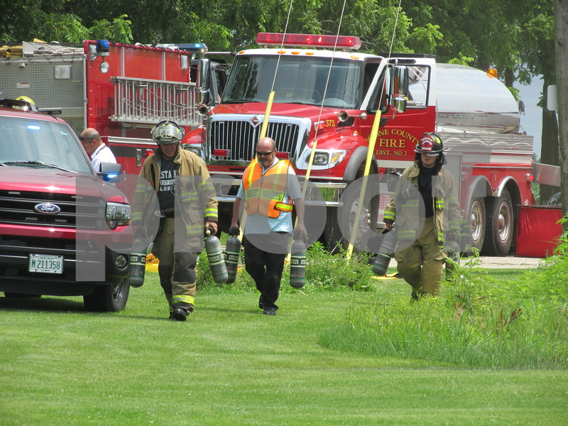 Emergency personnel cope with the muggy heat after fighting a fire at U.S. Chrome Corp. of Illinois, 305 Herbert Road.