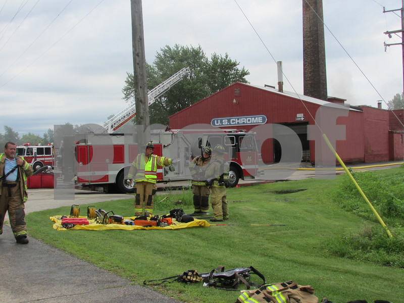 Firefighters hydrate and break down gear Monday afternoon at U.S. Chrome Corp. of Illinois, 305 Herbert Road, where it took about an hour to put out a fire. No injuries were reported.