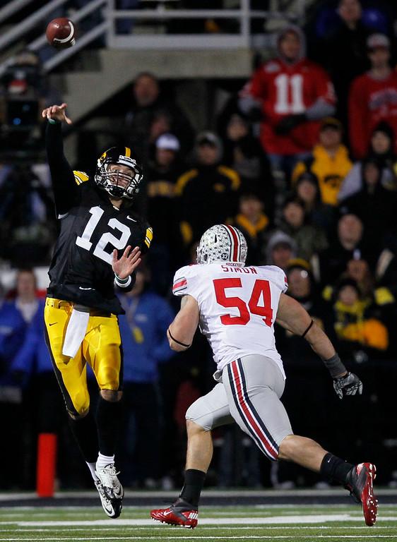 . Iowa quarterback Ricky Stanzi, left, passes over Ohio State defensive lineman John Simon during the second half of an NCAA college football game, Saturday, Nov. 20, 2010, in Iowa City, Iowa. Ohio State won 20-17. (AP Photo/Charlie Neibergall)