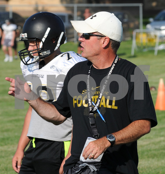 Sycamore High School football Head Coach Joe Ryan instructs players during a mini camp workout on Wednesday, July 11.  Steve Bittinger - For Shaw Media