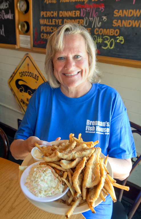 . News-Herald file Sharon Hill, owner of Brennan\'s Fish House, displays a Perch Dinner, a favorite at her Grand River restaurant.