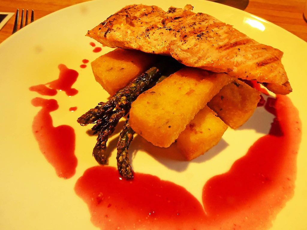 . Janet Podolak � The News-Herald <br> A blackberry thyme au jus adds its colorful flavor to Faroe Island salmon atop polenta fries with grilled asparagus at newly opened Fourk.