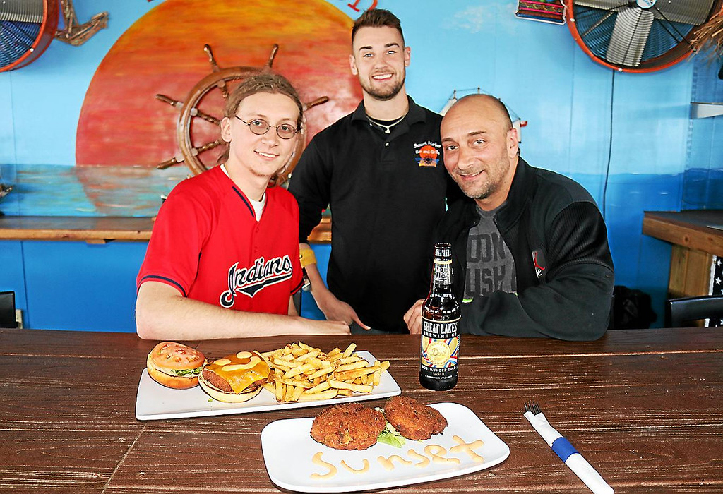 . Jonathan Tressler � The News-Herald From left, Sunset Harbor Bar & Grille manager Max Moore, bartender Colin O\'Brien and sous chef Albert Budy pause for a portrait behind two of the restaurant\'s signature dishes: The Mad Crabber crab cake sandwich with fries and a pair of crab cakes, sans sandwich fixings, served as an appetizer.