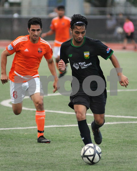 DeKalb County United's Antonio Reyes (right) moves the ball up field in first half action against Aurora Borealis on Friday, July 13 in DeKalb.  Steve Bittinger - For Shaw Media