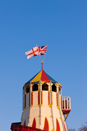 English and British flags on top of funfair castle, Ealing, W5, London, United Kingdom