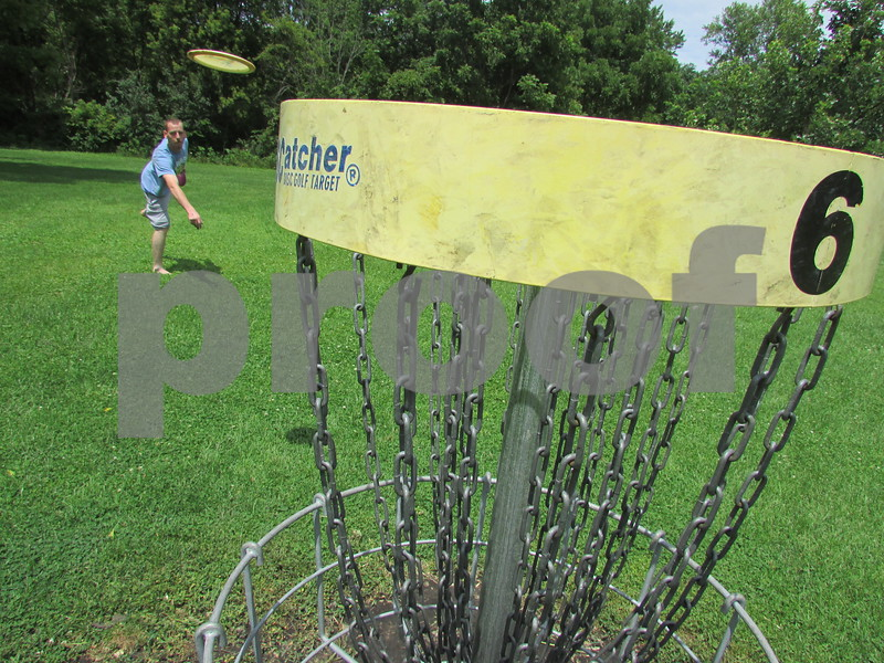 Photos by Christopher Heimerman - cheimerman@shawmedia.com<br /> Daniel Johnson, 28, of Genoa putts on the sixth hole of the disc golf course at Prairie Park in DeKalb around midday Friday. Johnson, who said he's moving to Malta soon, said the course is among his favorites, and that the DeKalb Disc Golf group is pitching the city on expanding the nine-hole course to 18 buckets.