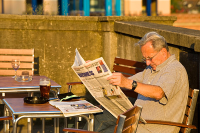 Man relaxing and reading newspaper at The Angel Pub by Thames River, Henley-on-thames, United Kingdom
