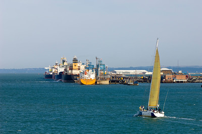 Yacht sailing by harbour terminal, Southampton, United Kingdom