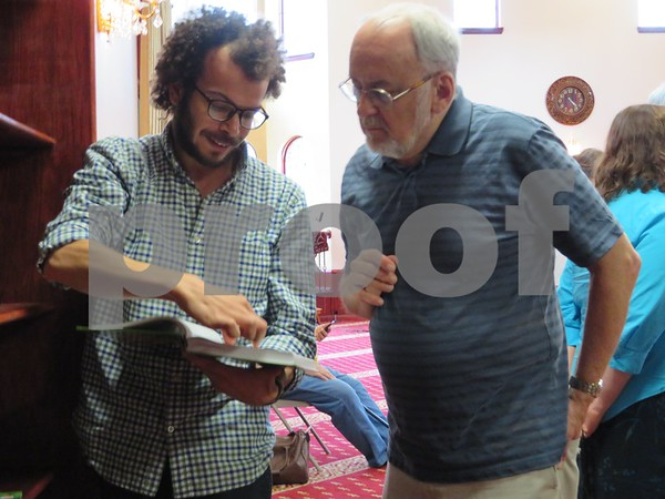 Osama Mohsen (left) shows Jan Bach (right) a copy of the Quran during the question and answer session at the Islamic Center of DeKalb, 801 Normal Road, which was before the Beloved Community dinner Sunday at St. Paul Episcopal Church, 900 Normal Road.
