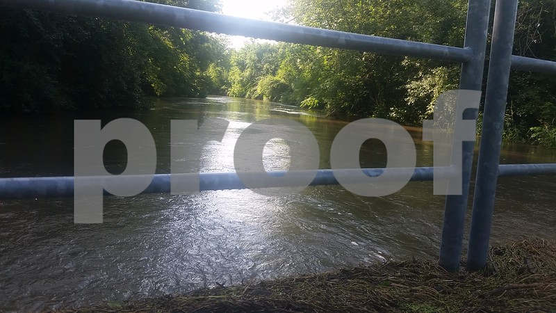 Christopher Heimerman - cheimerman@shawmedia.com<br /> The Kishwaukee River rolls along and creeps within about an inch of the top of the foot bridge at Prairie Park in DeKalb. The river was closed Saturday morning in DeKalb County, and officials said they will announce when it's reopened.