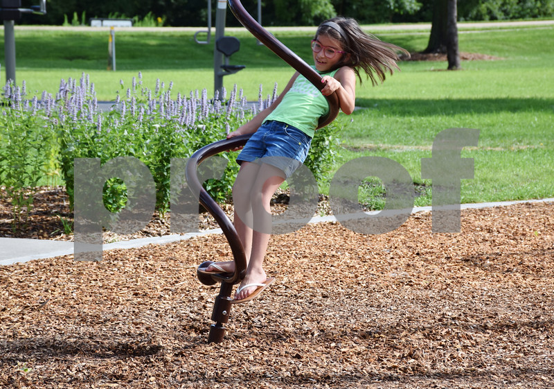 Seven-year-old Mackenzie Collins of DeKalb enjoys the new playground equipment at Lions Park, 700 W. Taylor St. in DeKalb. In addition to all-new playground equipment, the park now features sand volleyball, bags, horseshoes, a half basketball court, a picnic shelter, a council ring, a rock outlook over the Kishwaukee River and a blacktop path winding through a pine grove.