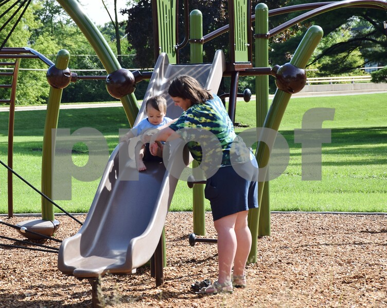 Maria Nihei of DeKalb plays on the slide with her 1-year-old son Clark at the newly-reopened and renovated Lions Park, 700 W. Taylor St. in DeKalb. Lions Park's grand reopening celebration on Saturday, July 22, included a ribbon cutting and free refreshments.