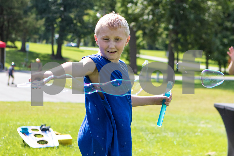Sam Buckner for Shaw Media.<br /> Landon Schindewolf (8) uses a bubble wand at the Family Fun Fest on Tuesday July 25, 2017 at Hopkins Park.