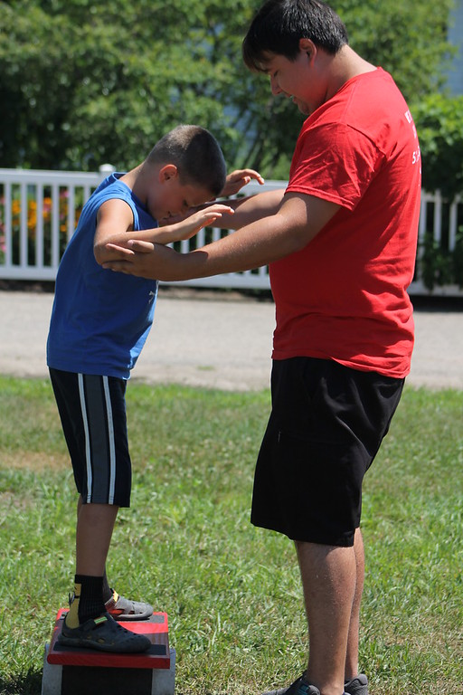 . Alban Schneider of the Cincinnati Circus helps  Mac Schwartz, 9, of Montville,get his balance on the balance board after his circus  performance at the 2018 Lake County Fair on July 25. Kristi Garabrandt - The News-Herald
