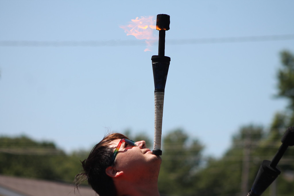 . Alban Schneider of the Cincinnati Circus balances a fire wand on his chin at the beginning of his fire juggling act  during his July 25,  performance at the 2018 Lake County Fair. Kristi Garabrandt - The News-Herald