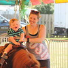 Maureen Moore, Lakewood, takes her son George, 15 months, on the pony rides at his first visit to the fair on July 25.<br /> Kristi Garabrandt - The News-Herald