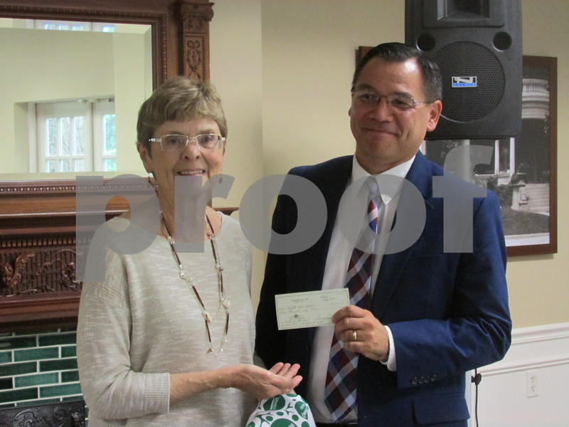 Sharon Tourville (left), treasurer for the DeKalb Rotary Club, presents a $2,000 check to DeKalb Park Board President Phil Young (right) during the board's Thursday meeting. The money will go toward improvements to the 1.3-mile Nature Trail and was collected from a fundraiser in May to help this cause.