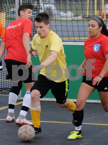 Sam Misch of Sycamore moves the ball for the Pavement Pineapples in the DKCU Street Soccer Tournament on Friday in Sycamore.  Steve Bittinger - For Shaw Media