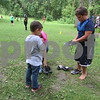 Guicho Martinez, 10, of Sycamore, puts his shoes on while his brother Eli, 6, looks on before joining fellow campers in a game of capture the flag Thursday at Walcamp Outdoor Ministries and Retreat Center. The brothers were selected for a week of camp through the Maria Ridulph Memorial Fund.