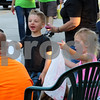 DeKalb residents Brayden MacNeille, 4, and Kyleigh MacNeille, 2, collect candy and watch the Kishwaukee Fest parade Friday in DeKalb.