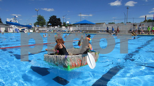 Aimee Barrows for Shaw Media<br /> Stacey Veldhuizen (front) and Cassie Lexa race to the side of Hopkins Pool during in the Cardboard Boat Regatta on Saturday in DeKalb. The duo won the event after placing second in the last year's inaugural regatta.
