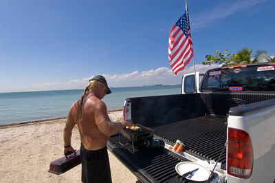 Man having a barbecue by his pick-up truck on the beach in Key B