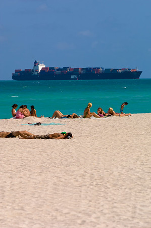 People relaxing on beach with container ship passing behind, South Beach, Miami, Gold Coast, Florida, United States of America