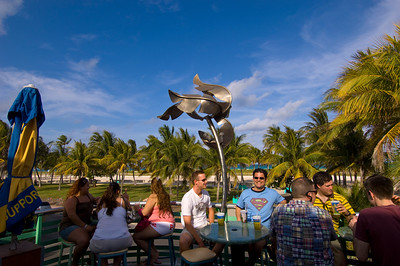 Youn people having a drink in a bar overlooking Ocean Drive, South Beach, Miami, Florida, USA