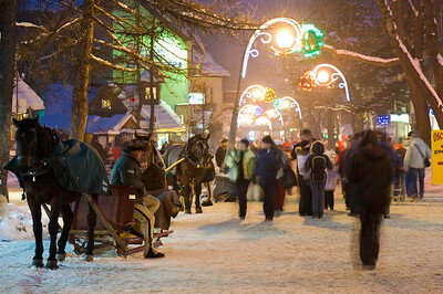People strolling and shopping on Krupowki Street at night, Zakopane, Tatra Mountains, Podhale Region, Poland