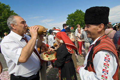 Villagers in traditional Bulgarian folk dress greet guests, tour