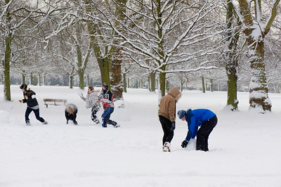 Young people playing in Walpole Park covered in February snow, Ealing, W5, London, United Kingdom
