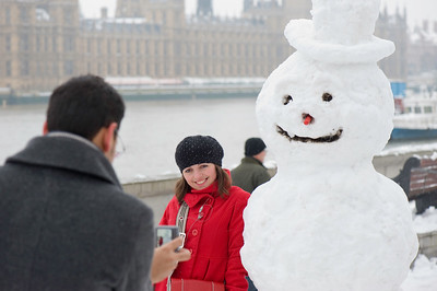 Tourists posing with snowman on Albert Embankment, London, United Kingdom