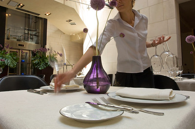 Waitress setting a table at a restaurant in Hotel Stary, Old Tow