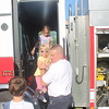 Kristi Garabrandt - The News-Herald<br /> Eastlake fire Lt. Jeff Kirkner helps Claire Jackson, 3, of Eastlake, down out of the fire truck while her sister Kellie, 8, follows behind during Eastlake's National Night Out.