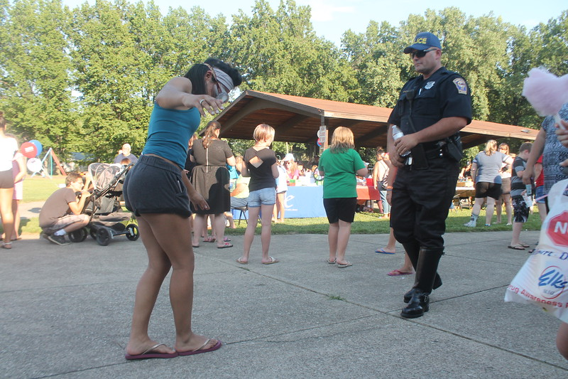 Kristi Garabrandt - The News-Herald<br /> Shyanne Ciero, 18, Eastlake wears googles that simulate how an intoxicated person sees while she tries to take a mock sobriety test while Eastlake  officer Cole Eden looks on during Eastlake's National Night Out.