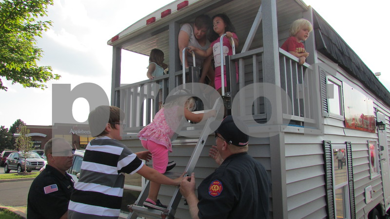Children learn how to escape from a burning house Tuesday during National Night Out in DeKalb.  Aimee Barrows for Shaw Media