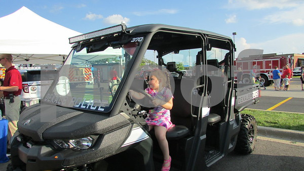 Lucy Schneider, 5, of DeKalb plays in a DeKalb Police Department vehicle Tuesday during National Night Out in DeKalb.  Aimee Barrows for Shaw Media