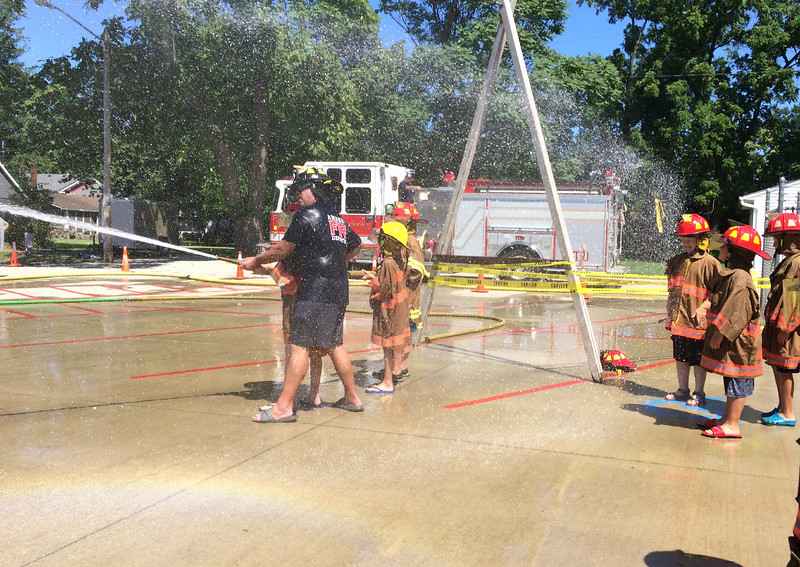 Carol Harper — The Morning Journal <br> Amherst firefighter Chuck Boesel helps a youngster shoot for the yellow jug during Kids Water Fights August 5, 2017, at Amherst Fire Station at 414 Church St. in Amherst.
