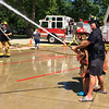 Carol Harper — The Morning Journal <br> Amherst firefighter Chuck Boesel helps a youngster shoot for the yellow jug during Kids Water Fights Aug. 5, 2017, at Amherst Fire Station at 414 Church St. in Amherst.