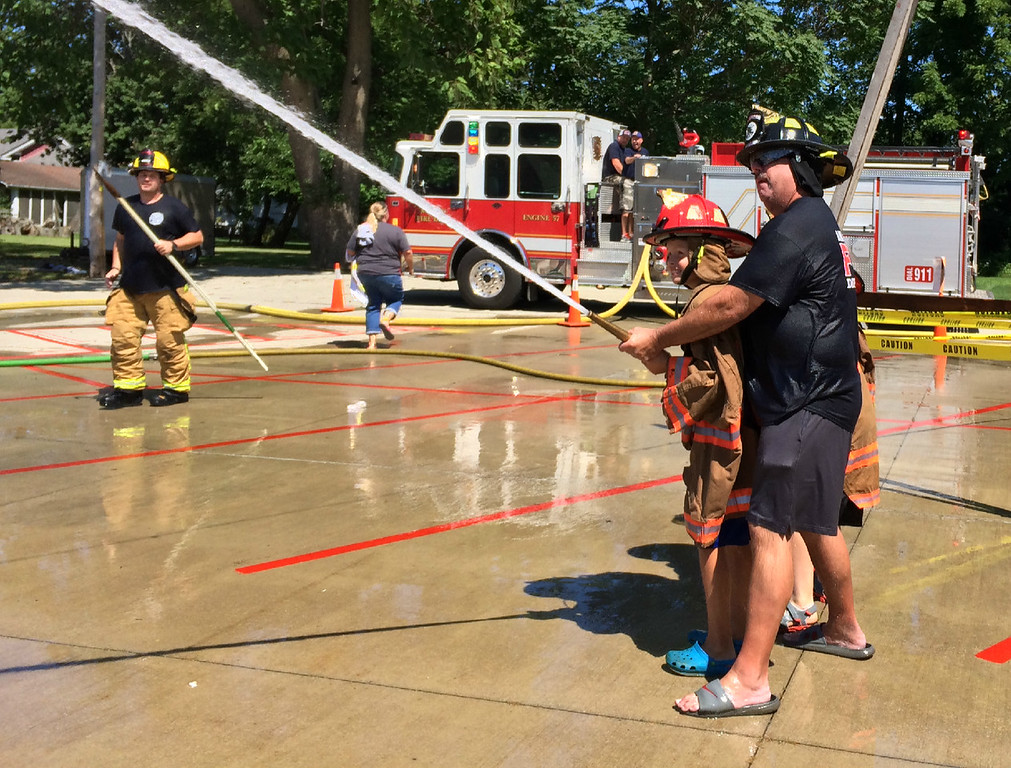 . Carol Harper � The Morning Journal <br> Amherst firefighter Chuck Boesel helps a youngster shoot for the yellow jug during Kids Water Fights Aug. 5, 2017, at Amherst Fire Station at 414 Church St. in Amherst.