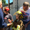 Carol Harper — The Morning Journal <br> Learning the ways of the firehouse, seven-year-old Xzander Garra slaps five after donning turnout gear for Kids Water Fights Aug. 5, 2017, at Amherst Fire Department at 414 Church St. in Amherst. Behind Xzander is his grandfather, David Garra, Amherst.