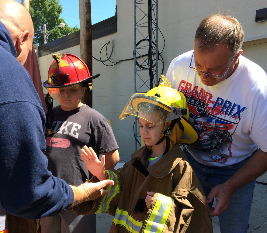 . Carol Harper � The Morning Journal <br> Learning the ways of the firehouse, seven-year-old Xzander Garra slaps five after donning turnout gear for Kids Water Fights Aug. 5, 2017, at Amherst Fire Department at 414 Church St. in Amherst. Behind Xzander is his grandfather, David Garra, Amherst.