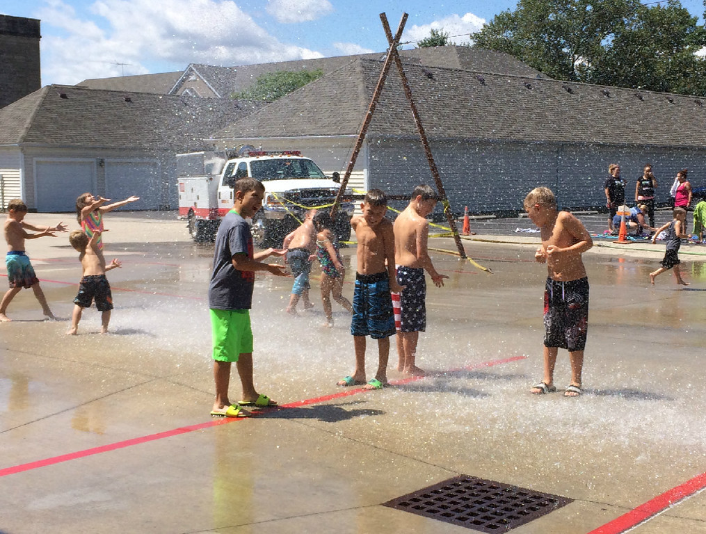 . Carol Harper � The Morning Journal <br> Squeals of delight pierced the quiet morning each time competition paused and firefighters blasted a stream of water from the truck at Kids Water Fights Aug. 5, 2017, at Amherst Fire Station at 414 Church St. in Amherst.
