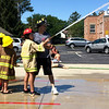 """Carol Harper — The Morning Journal <br> A girl's fire coat says, """"Chief,"""" as she points a powerful stream of water with firefighter Adam Willard during Kids Water Fights Aug. 5, 2017, at Amherst Fire Department at 414 Church St. in Amherst."""