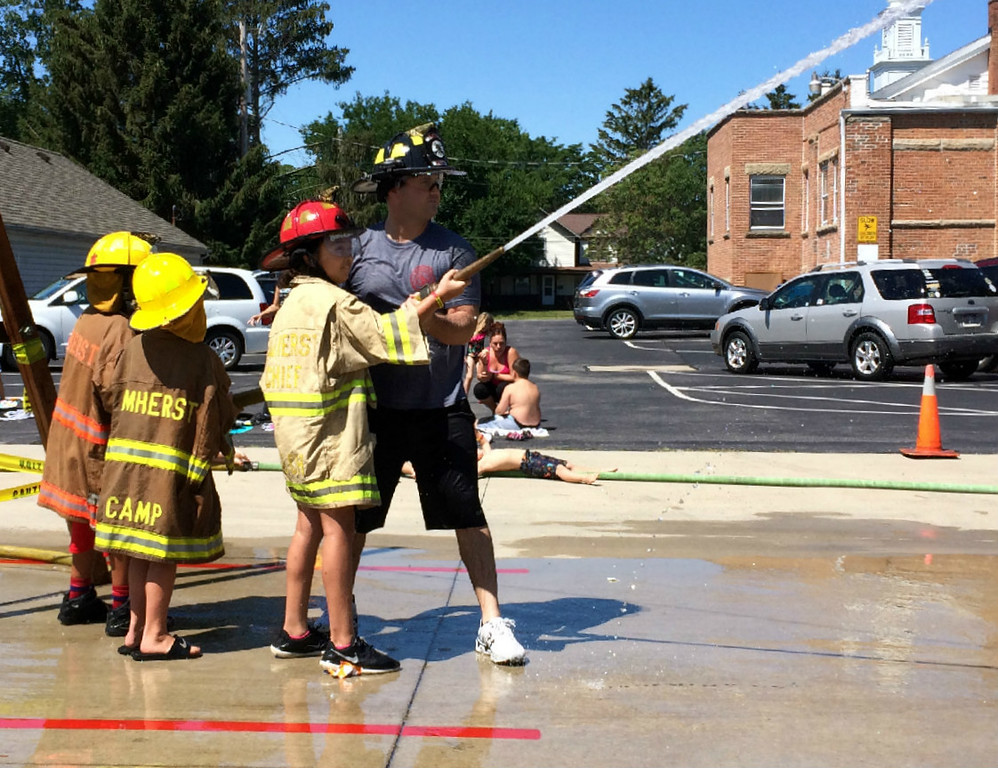 ". Carol Harper � The Morning Journal <br> A girl\'s fire coat says, ""Chief,\"" as she points a powerful stream of water with firefighter Adam Willard during Kids Water Fights Aug. 5, 2017, at Amherst Fire Department at 414 Church St. in Amherst."