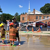 Carol Harper — The Morning Journal <br> Seven-year-old Xzander Garra aims a fire hose with Amherst firefighter Adam Willard Aug. 5, 2017, at Kids Water Fights at the fire station at 414 Church St. in Amherst. Xzander attended the event with his grandfather David Garra and great-grandfather Charlie Garra, a former assistant fire chief.