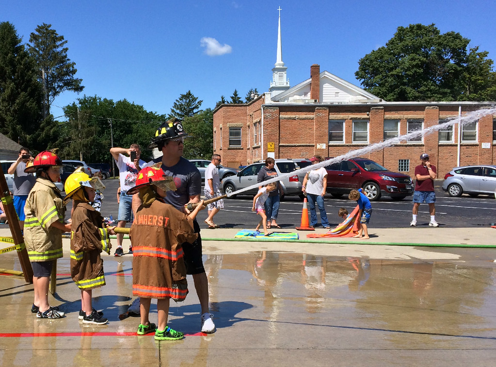 . Carol Harper � The Morning Journal <br> Seven-year-old Xzander Garra aims a fire hose with Amherst firefighter Adam Willard Aug. 5, 2017, at Kids Water Fights at the fire station at 414 Church St. in Amherst. Xzander attended the event with his grandfather David Garra and great-grandfather Charlie Garra, a former assistant fire chief.