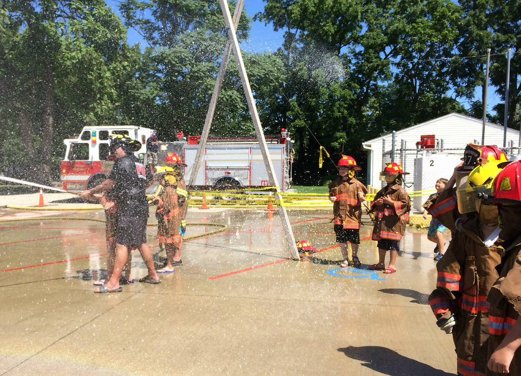 . Carol Harper � The Morning Journal <br> Overspray from a raging battle served as a fringe benefit of Kids Water Fights Aug. 5, 2017, at Amherst Fire Station at 414 Church St. in Amherst.