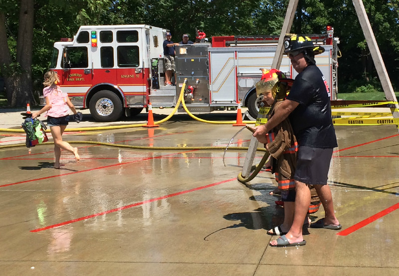 Carol Harper — The Morning Journal <br> Firefighter Chuck Boesel waits with a youngster for word to start a next battle at Kids Water Fights Aug. 5, 2017, at Amherst Fire Station at 414 Church St. in Amherst.
