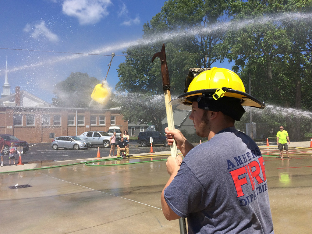 . Carol Harper � The Morning Journal <br> Fifteen-year-old Zac Boesel, a Marion L. Steele sophomore, holds a fire hook and supervises the action at Kids Water Fights at Amherst Fire Station at 414 Church St. in Amherst.